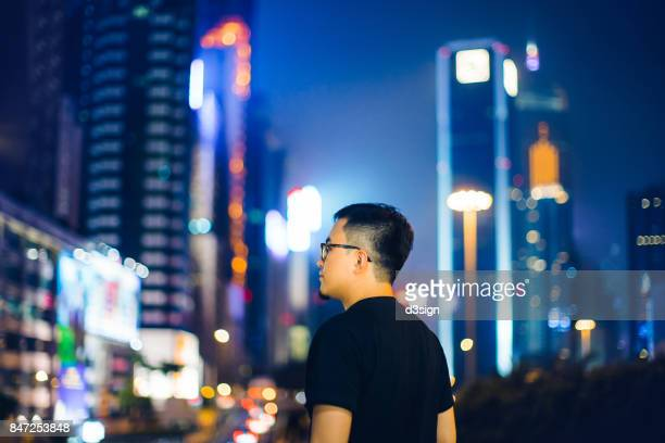 Portrait of young man in city against illuminated city skyline at night