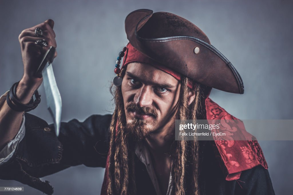 Portrait Of Young Man In Costume Holding Knife Against Gray Background : Photo