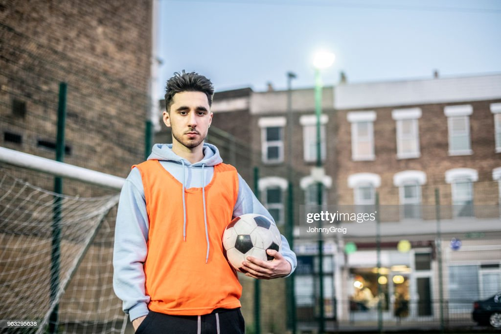 Portrait of young man in football bib holding ball : Stock Photo