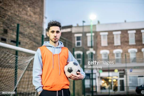 Portrait of young man in football bib holding ball