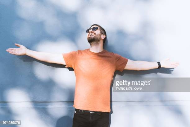 portrait of young man in front of blue wall - arms outstretched stock pictures, royalty-free photos & images