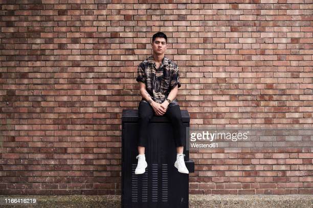 portrait of young man in front of brick wall - sitting stock pictures, royalty-free photos & images