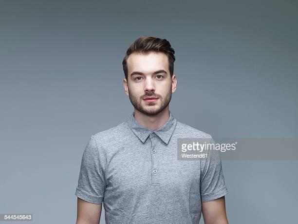 portrait of young man in front of grey background - stoppelbart stock-fotos und bilder