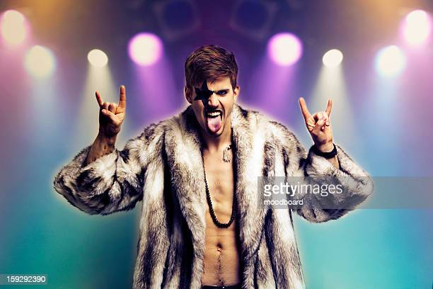 Portrait of young man in fur coat making rebellious hand gestures in rock concert