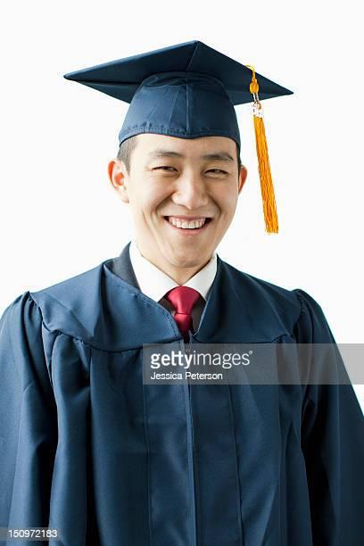Portrait of young man in graduation gown, studio shot