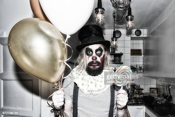 Portrait Of Young Man In Halloween Costume Holding Balloons And Candy