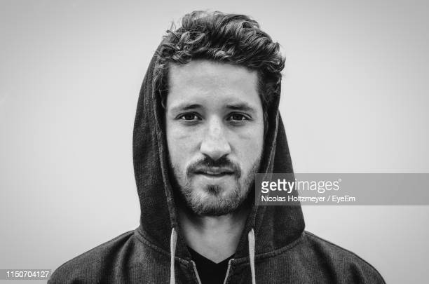 portrait of young man in hooded shirt against gray background - alleen één jonge man stockfoto's en -beelden