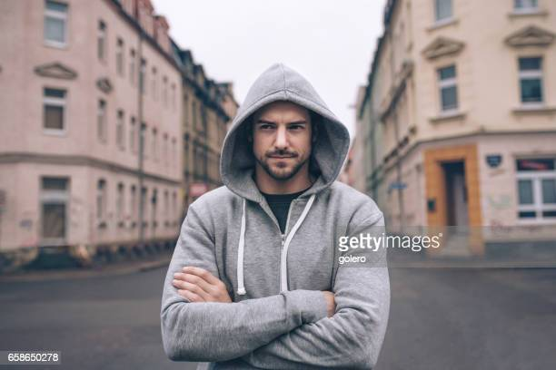 portrait of young man in hoody in city streets