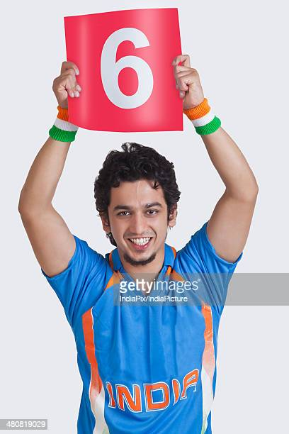 Portrait of young man in Indian cricket jersey signaling a six over white background