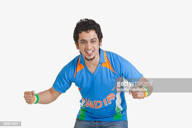 Portrait of young man in Indian cricket team jersey cheering over white background