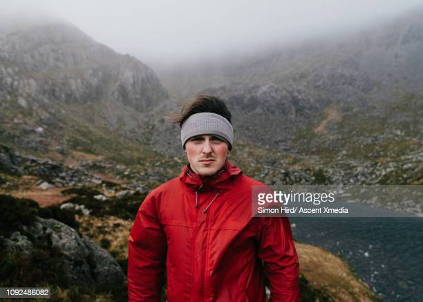 Portrait of young man in mountain moor, on rainy day