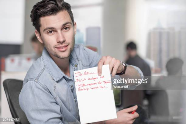 Portrait of young man in office showing to do list