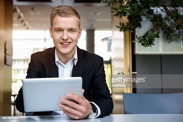 portrait of young man in office using touchscreen on digital tablet - 男性一人 ストックフォトと画像