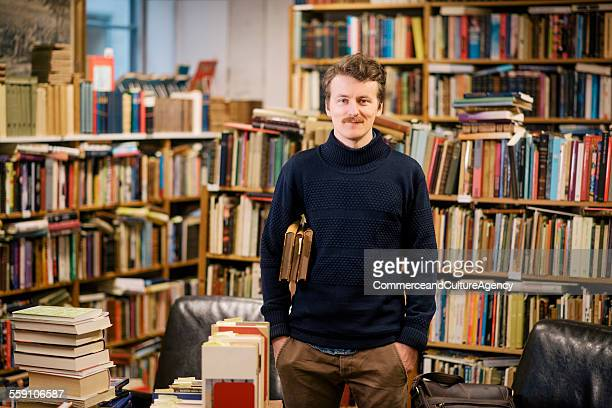 portrait of young man in second hand bookstore - hands in pockets stock pictures, royalty-free photos & images