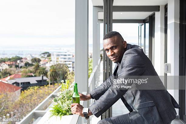 Portrait of young man in suit on balcony, Cape Town, South Africa