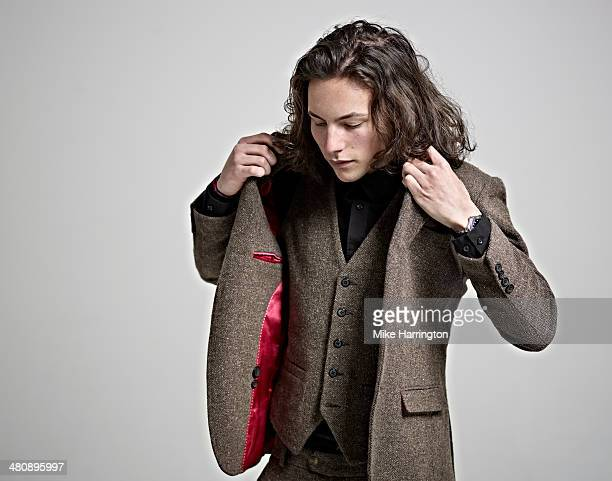 portrait of young man in suit putting on jacket. - giacca da abito foto e immagini stock