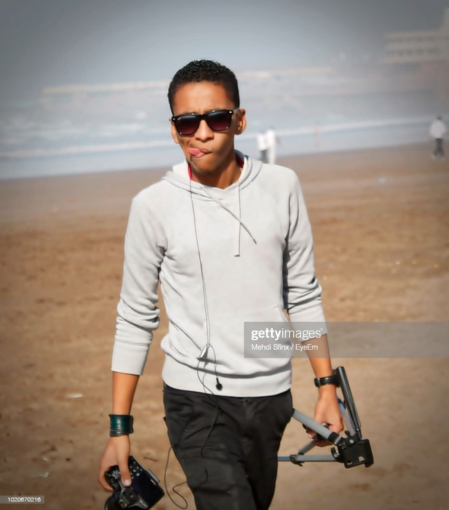 babbfcf77444 Portrait Of Young Man In Sunglasses Sticking Out Tongue At Beach : Stock  Photo