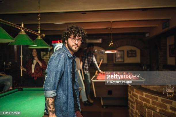 ritratto di giovane al pub mentre gioca a snooker e si diverte con gli amici al pub. - club football foto e immagini stock