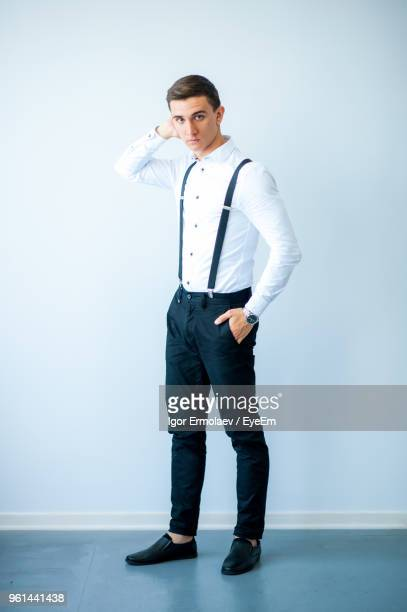 Portrait Of Young Man In Tuxedo Standing Against White Background