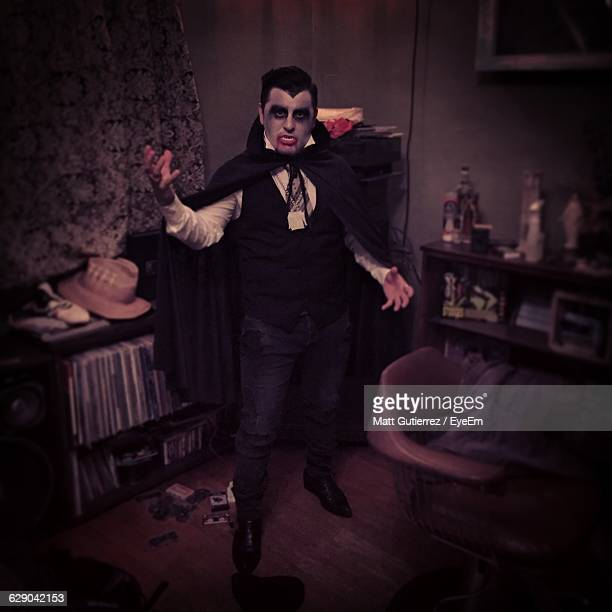 portrait of young man in vampire costume standing at home during halloween - count dracula stock photos and pictures