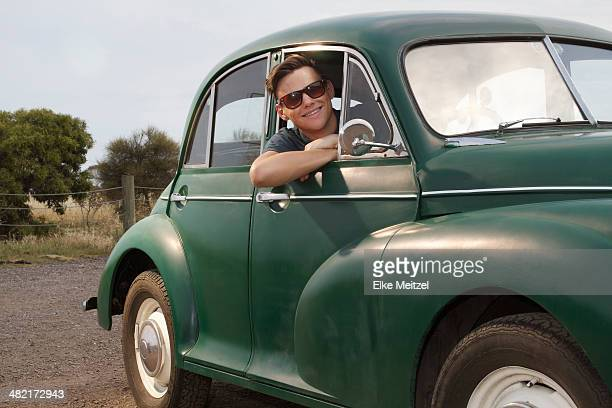 Portrait of young man in vintage morris minor