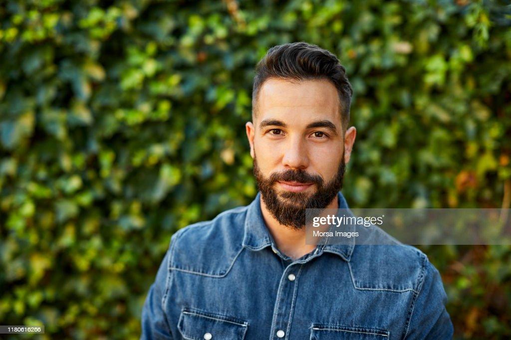 Portret van de jonge man in geel t-shirt in de achtertuin : Stockfoto