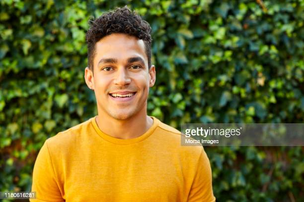 portrait of young man in yellow t-shirt at backyard - curly stock pictures, royalty-free photos & images