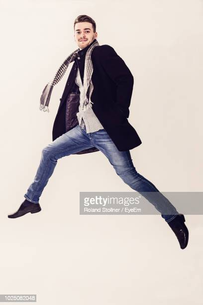 portrait of young man jumping against white background - coat ストックフォトと画像