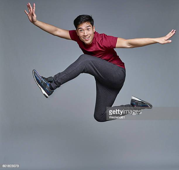 Portrait of young man jumping in the air in front of grey background