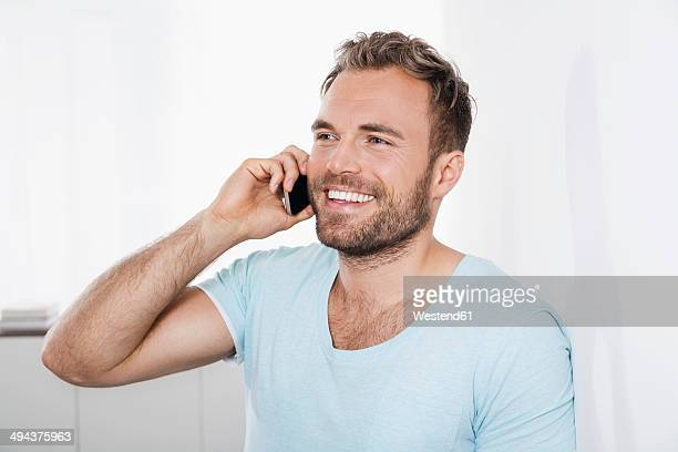 Portrait of young man leaning against wall telephoning with smartphone