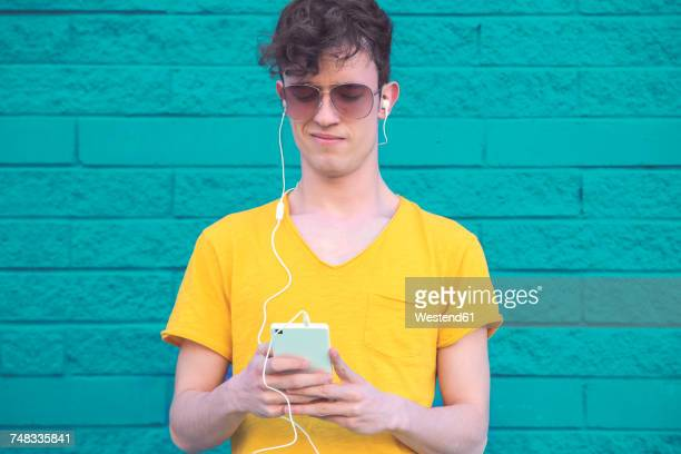 portrait of young man listening music with smartphone and earphones in front of blue brick wall - arrogance stock pictures, royalty-free photos & images