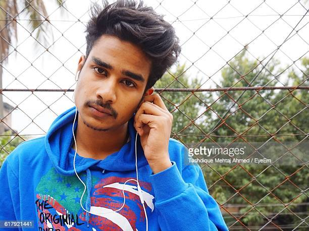 Portrait Of Young Man Listening To Music Against Fence