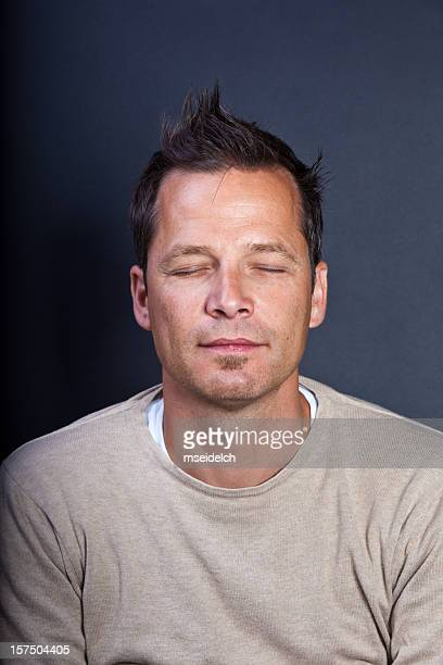 Portrait of young man looking at camera with closed eyes