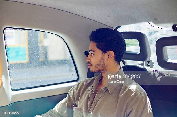 portrait of young man looking out of taxi window