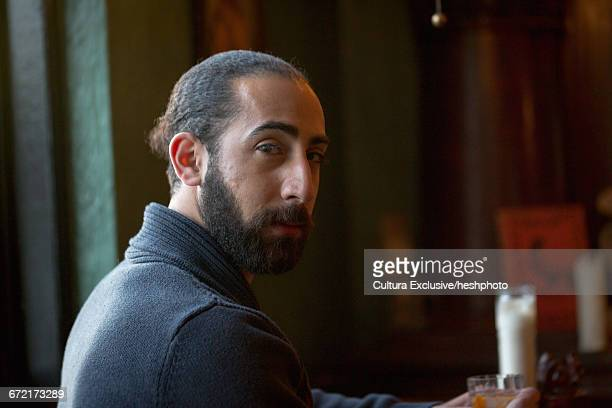 portrait of young man looking over his shoulder in recreational bar - heshphoto stock pictures, royalty-free photos & images