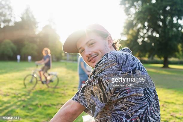 Portrait of young man looking over his shoulder in sunlit park