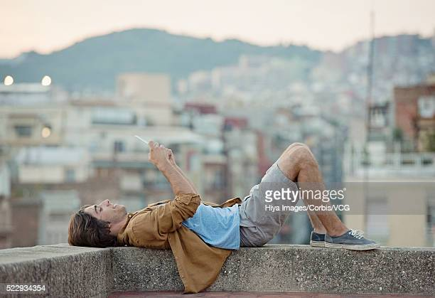 Portrait of young man lying on parapet of roof terrace, using digital tablet