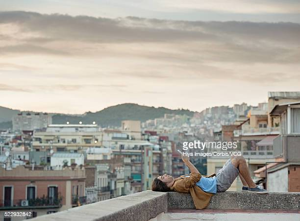Portrait of young man lying on parapet of roof terrace, using tablet computer