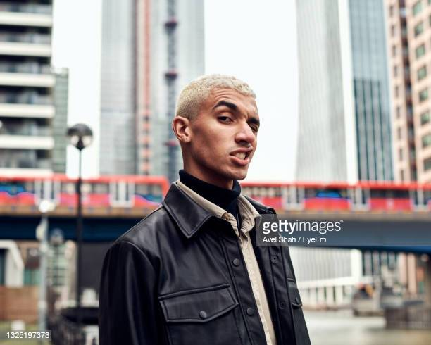portrait of young man making face against building - menswear stock pictures, royalty-free photos & images