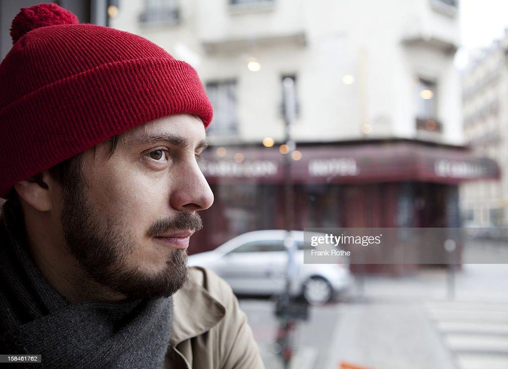 portrait of young man near a window to the street : Bildbanksbilder