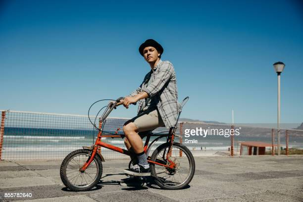 portrait of young man on bicycle on the boardwalk - offbeat stock photos and pictures
