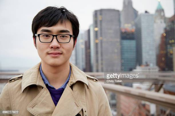 Portrait of young man on Brooklyn Bridge with skyscrapers in background