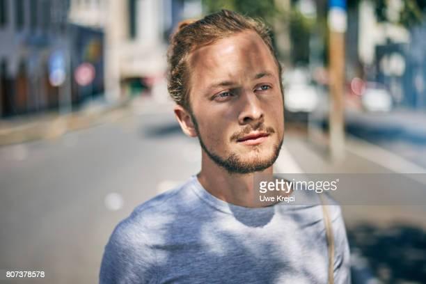 portrait of young man on city road - introspektion stock-fotos und bilder