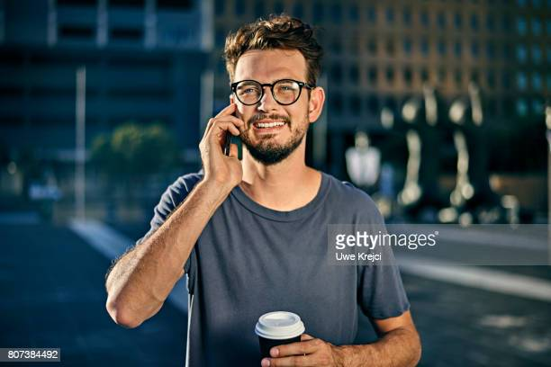 portrait of young man on phone - navy blue stock pictures, royalty-free photos & images