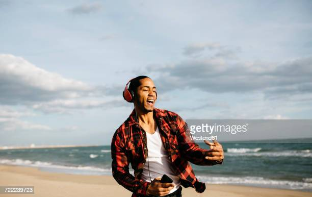 portrait of young man on the beach singg and dancing while listening music with headphones - singing stock pictures, royalty-free photos & images
