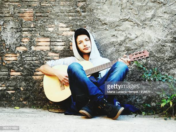 Portrait Of Young Man Playing Guitar While Sitting Against Wall