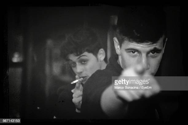 Portrait Of Young Man Pointing Finger While Friend Smoking Cigarette Behind