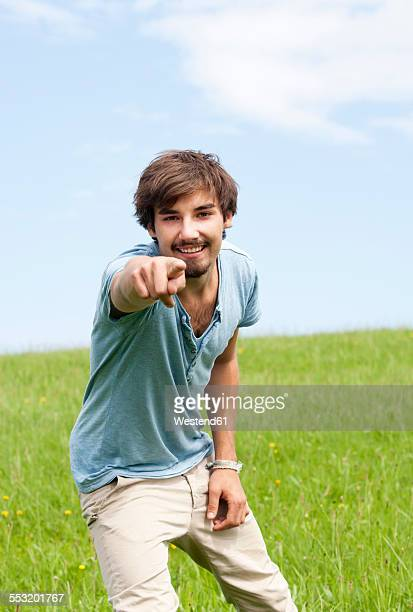 Portrait of young man pointing on viewer standing on a meadow