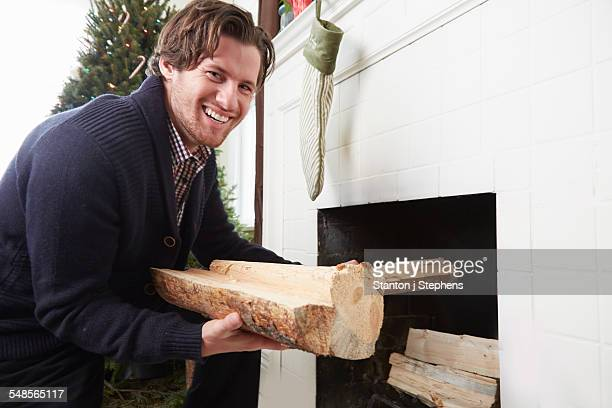 Portrait of young man preparing logs for fire at christmas
