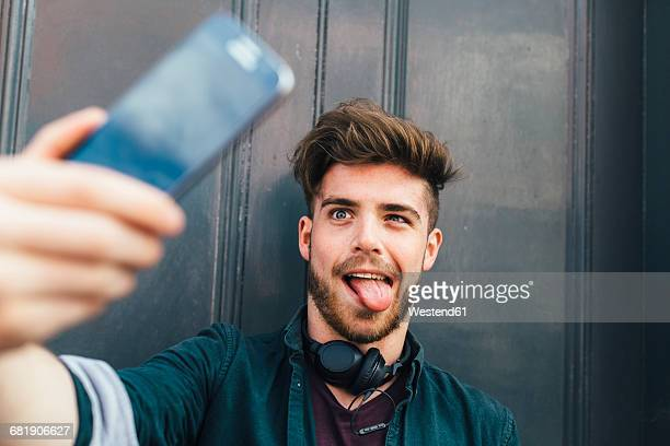 portrait of young man pulling funny face taking selfie with smartphone - ポンパドール ストックフォトと画像